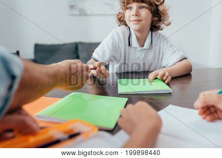Father Passing Pen To Adorable Curly Son