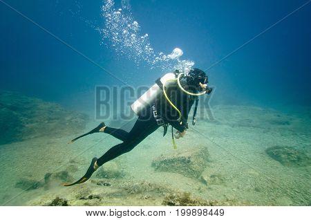 Scuba diver exploring the bottom underwater blue color image