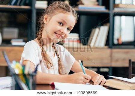 happy smiling little girl writing in notebook and doing homework