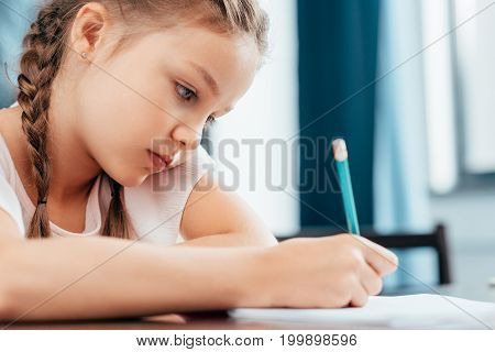 focused serious little girl writing in notebook and doing homework