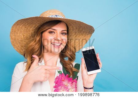 Happy smiling woman showing cell phone with black screen and gesturing thumb up, on a blue background.