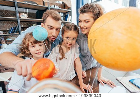 Adorable Family Making Solar System Model For School Project