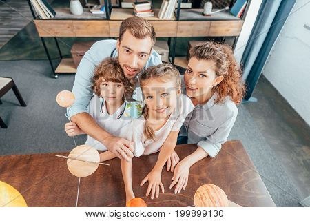 Top View Of Happy Family With Solar System Model For School Project
