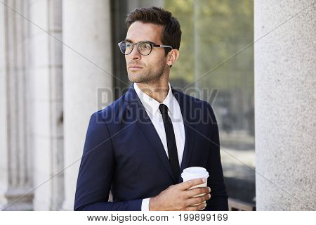 Young Contemplative businessman with coffee and glasses