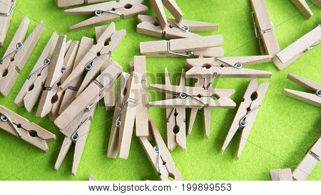 many wooden clothespins on a green background
