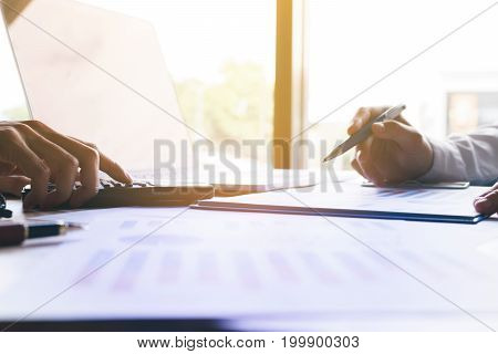 Business People Calculating And Writing On Notebook With Laptop For Searching Data Information.