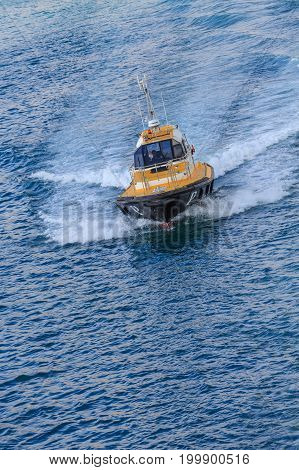 A black and yellow pilot boat cutting through the blue water of Barcelona harbor