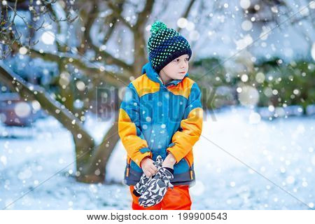 Funny little kid boy in colorful clothes playing outdoors during snowfall. Active leisure with children in winter on cold snowy days. Happy child on winter vacations in Sweden.