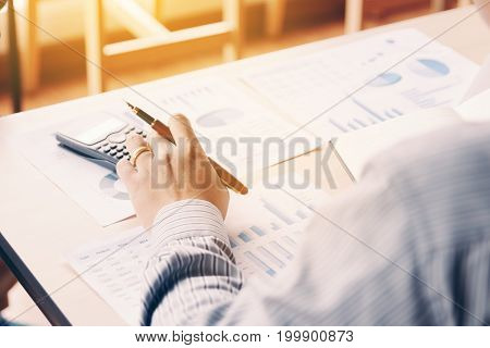 Rear View Of Business Asian Man Calculate With Analyze Result Summary Report On Desk In Company Offi