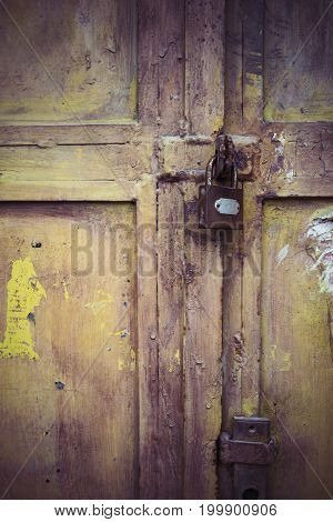 Weathered padlock and door with peeling paint