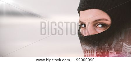 Portrait of female hacker wearing balaclava against defocused image of sky