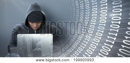 Focused male hacker using laptop  against panoramic shot binary codes on blue screen