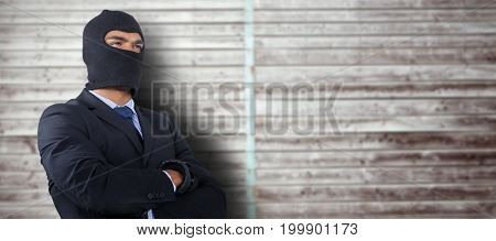 Male hacker standing with arms crossed against digitally generated grey wooden planks