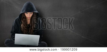 Young female hacker using laptop while sitting  against black wall