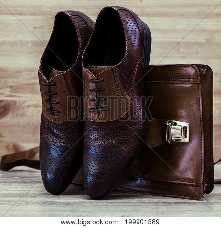 Stylish male brown shoes with handbag in wooden background