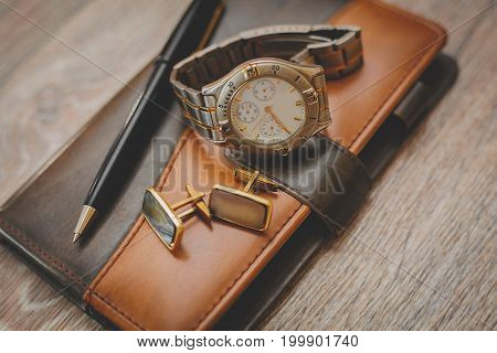 man different accessories and notepad in wooden background