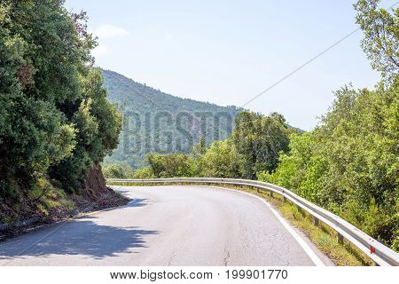 Daylight view to a road in mountains of Monterosso. Trees on background. Italy, Cinque Terre.