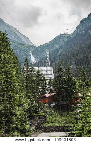 Carpathians nature landscape waterfall in Fagaras mountains and houses on foreground at Romania spectacular wilderness scenery.