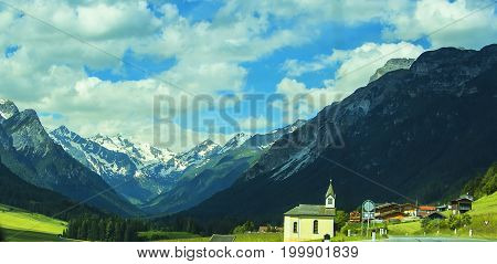 Background view of the panorama of the Alpine peaks, the sky and a beautiful Christian church in an alpine village in Tyrol