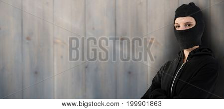 Portrait of female hacker standing with arms crossed against pale grey wooden planks