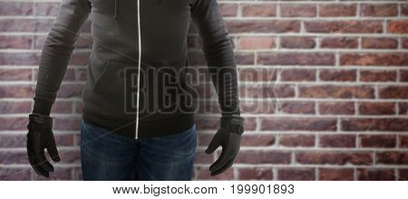 Robber wearing black hoodie against red brick wall