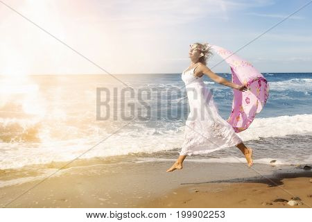 beautiful blond woman jumping on the beach and holding shawl in the wind