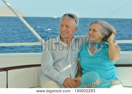 Smiling elderly couple resting on yacht in sea