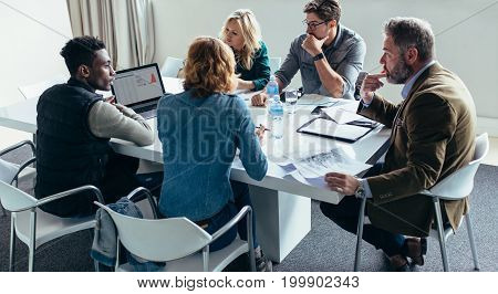 Modern business team working on new project during meeting and looking at laptop. Businessman giving presentation on laptop to colleagues