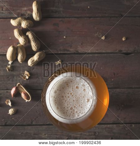 Top view of a glass of pale unfiltered beer with froth and some peanuts on a rustic wooden pub table. Focus on the froth