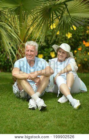 Elderly couple sitting on grass at hotel resort