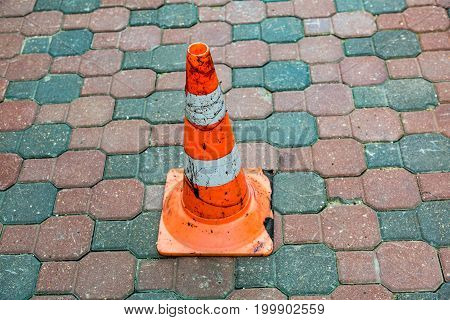 Plastic striped orange road sign in the form of a cone