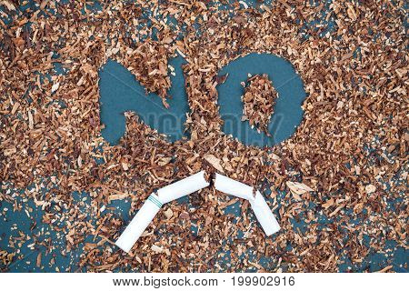 No Smoking Sign Made With Broken Cigarettes And Tobacco On Blackboard.