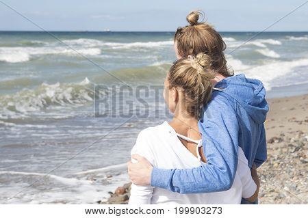 young couple by the ocean hugging each other