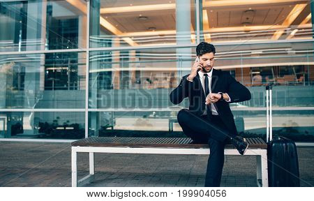 Business Traveler Talking On Phone And Checking Time
