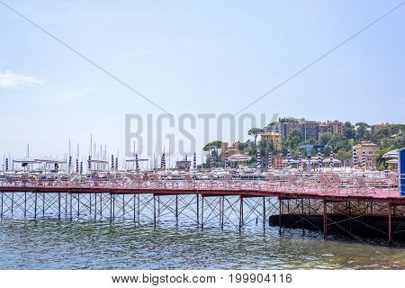 Beautiful view to Rapallo beach pier, blue sea and mountains. Italy beauties.