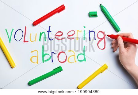 Woman writing text VOLUNTEERING ABROAD on white background