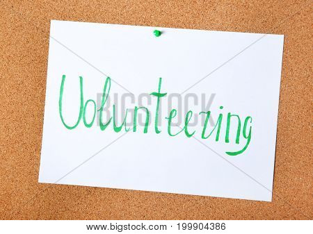 Sheet of paper with word VOLUNTEERING pinned to cork board