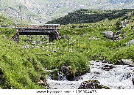 View of the Fagaras mountains water stream and famous Transfagarasan road in Carpathians Romania spectacular wilderness scenery.