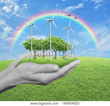 Wind turbines grass and trees in human hands over green grass with blue sky clouds and rainbow Ecological concept