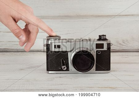 Hand pushing the button of a retro film camera on grey background.