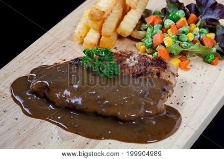 Close Up Steak Pork With Black Pepper Sauce, French Fries And Salad On Wood Plate.