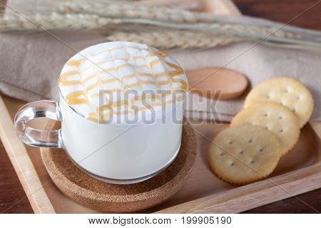 Close Up Hot Milk And Caramel On Top With Biscuits On Wooden Plate On Wooden Table For Breakfast.