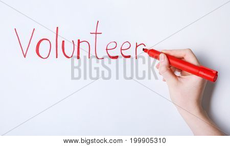 Woman writing word VOLUNTEER on white background