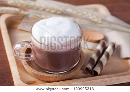 Close Up Hot Chocolate Milk With Snack On Wooden Plate On Wooden Table For Breakfast.