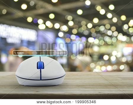 Search www button with wireless computer mouse on wooden table over blur light and shadow of shopping mall Searching system and internet concept