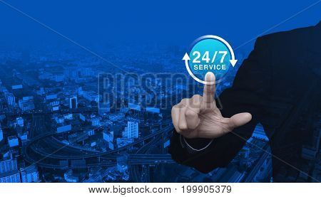 Businessman pressing button 24 hours service icon over modern city tower street and expressway Full time service concept