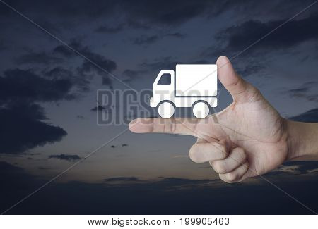 Truck delivery icon on finger over sunset sky Transportation business concept