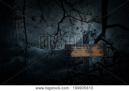 Cross over old fence dead tree moon and cloudy sky Spooky background Halloween concept
