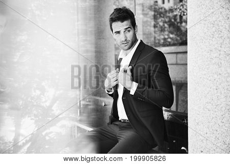 Posing businessman in suit sitting on bench looking away