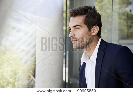 Young Contemplative businessman in suit looking away